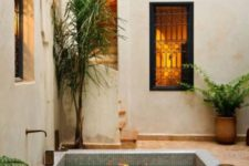 a boho Moroccan space with a plunge pool with benches inside, some tropical trees in planters and greenery