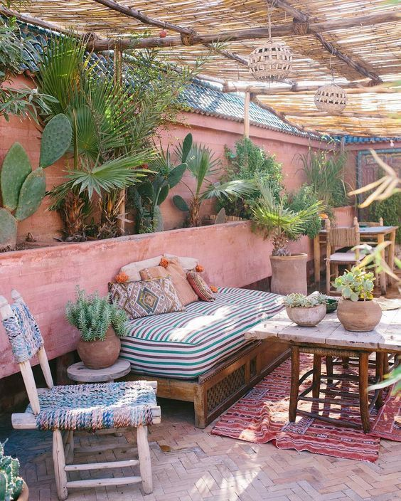 a boho desert terrace done in pink shades, with potted cacti and palm trees, printed linens and a printed rug
