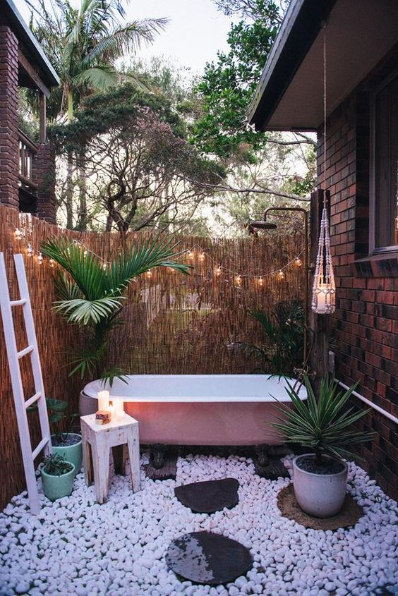 a boho outdoor bathroom with a privacy screen, a pink bathtub, white pebbles, potted greenery and lights and candles