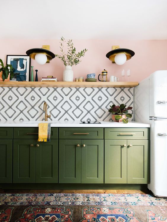 a bold boho kitchen with a pink wall, geometric tiles, a boho rug, green cabinets and gold touches