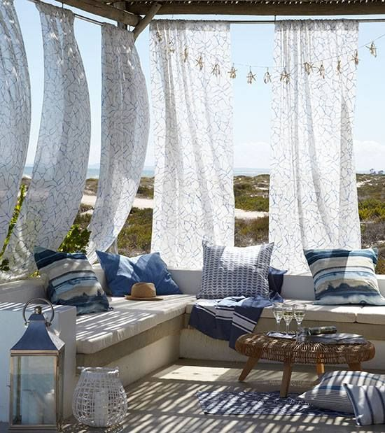 a breezy Mediterranean terrace with a concrete bench with printed pillows, candle lanterns, a rattan table and printed curtains