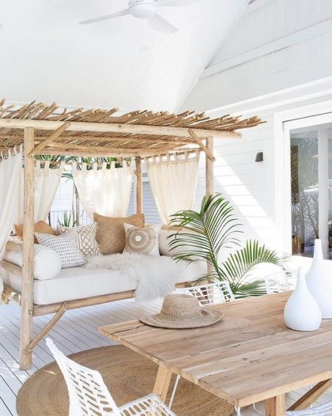 a breezy and airy tropical terrace done in neutrals with wooden furniture, printed pillows, some greenery