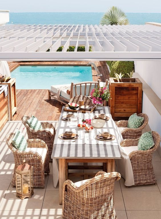 a bright Mediterranean terrace with rattan chairs, a wooden table and planters, printed textiles and bright blooms