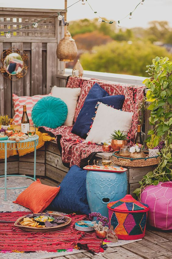 a bright boho Moroccan terrace with colorful textiles, colorful pillows, baskets and colorful fruniture