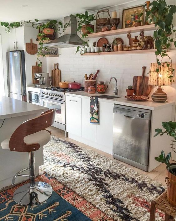 a bright boho kitchen with printed rugs, potted greenery, wooden tableware and warm colored porcelain