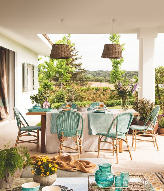 a cheerful Mediterranean terrace with turquoise chairs, textiles, glasses, greenery and blooms and wicker lamps