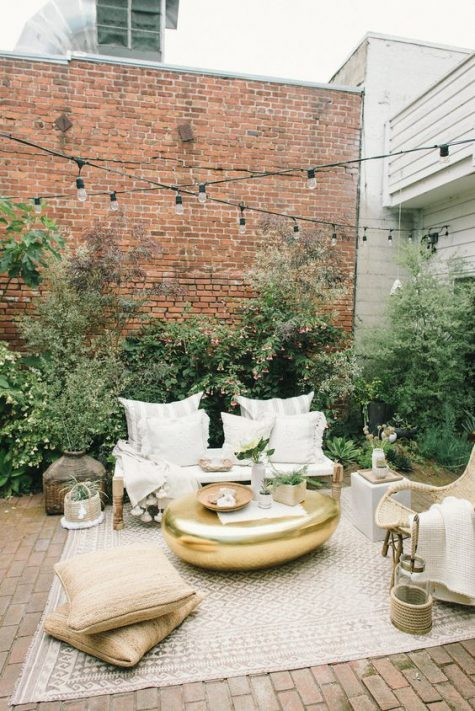 a chic eclectic neutral terrace with wooden and rattan furniture, stripes, gold touches and jute