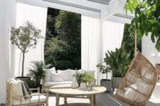 a chic tropical terrace with a hanging chair, rattan furniture, potted greenery is classics