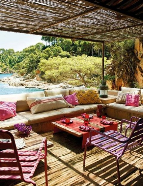 a colorful Mediterranean terrace with bright pink chairs, thrwos, bold textiles and candle lanterns plus a sea view