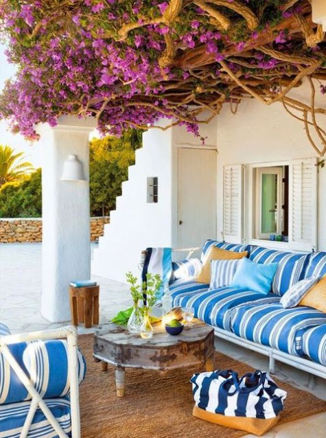 a colorful Mediterranean terrace with bright striped furniture, bright blooms over the terrace, a vintage table and a jute rug