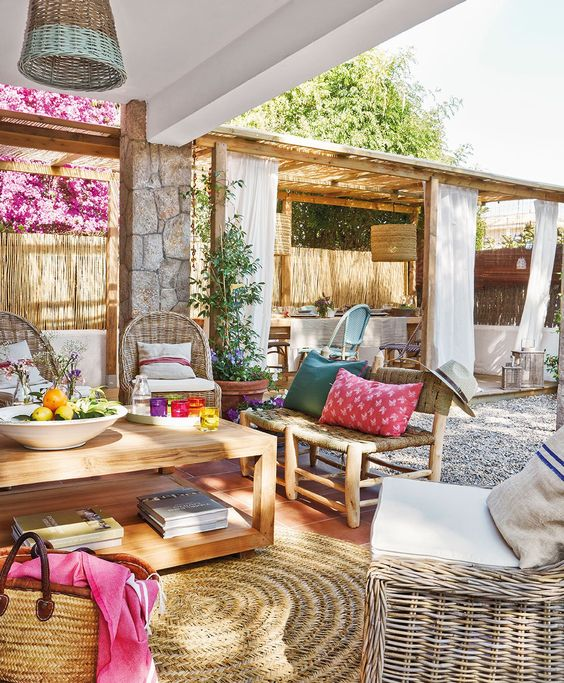 a colorful Mediterranean terrace with bright textiles and rattan furniture, wooden items, colorful accessories and potted greenery