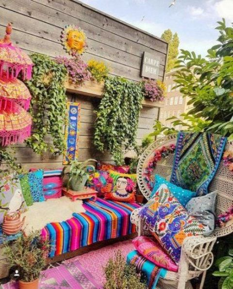 a colorful boho chic terrace with bright printed textiles, hanging greenery and rattan chairs and wooden furniture