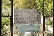 a contemporary backayrd with a small deck, metal chairs, some greenery and a plunge pool plus a wall for privacy