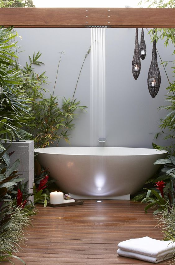 a contemporary bathroom with an oval tub, growing greenery, candles and a waterfall shower
