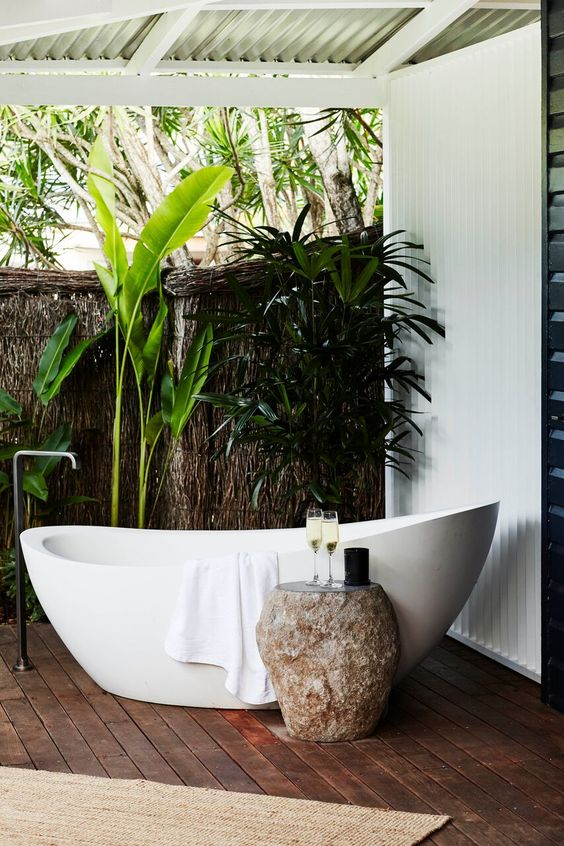 a contemporary luxe outdoor bathroom with shutters over it and a natural wall, greenery and a chic oval tub