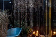 a contemporary space in a small yet full private courtyard, with pebbles on the floor, candles and a grey vintage bathtub