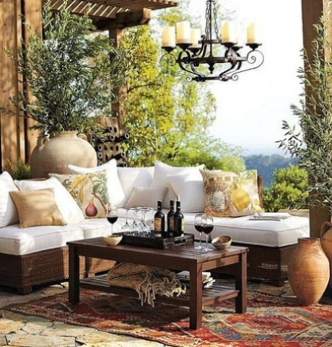 a cozy Mediterranean terrace with a wicker sofa, a printed rug, a vintage chandelier, potted greenery and printed throws