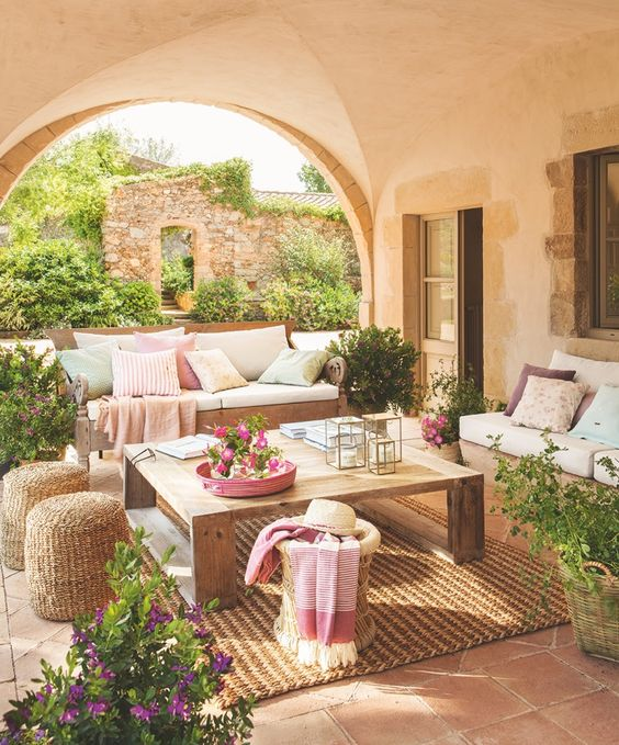 a cozy Mediterranean terrace with jute rugs and ottomans, wooden furniture, pastel textiles and potted greenery