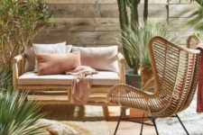 a cozy neutral boho desert terrace with a rattan chair, a wooden sofa, jute rugs, cacti and greenery