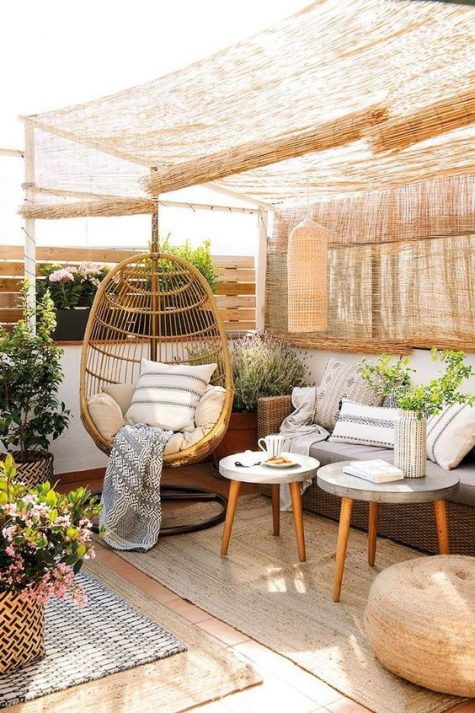 a cozy rustic terrrace in natural tones with wicker curtains, wicker furniture, a rattan chair and potted blooms and greenery
