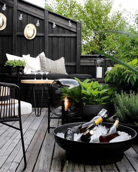 a dark Nordic terrace with blakc walls, planters and bowls, metal and wooden furniture, a catchy floor lamp and greenery that refreshes the space