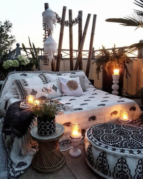 a gypsy inspired monochromatic patio with candle lanterns, potted greenery and printed textiles all over
