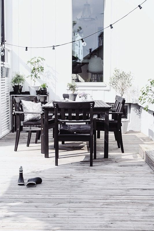 a laconic Nordic terrace with dark furniture, string lights and potted greenery plus all neutrals around