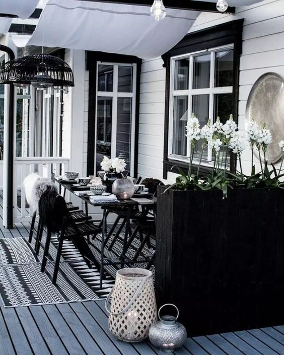 a laconic Scandinavian dining space with black furniture, a tall planter as a space divider, candle lanterns and pendant lamps