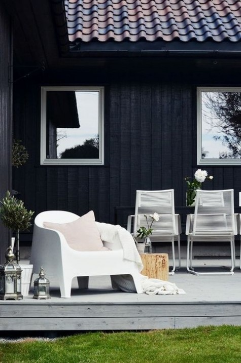 a laconic black and white terrace with metal chairs and a sculptural one, candle lanterns and some greenery and blooms