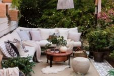 a lively neutral terrace with a corner sofa, a white pendant lamp, greenery and some boho accessories decorated for fall