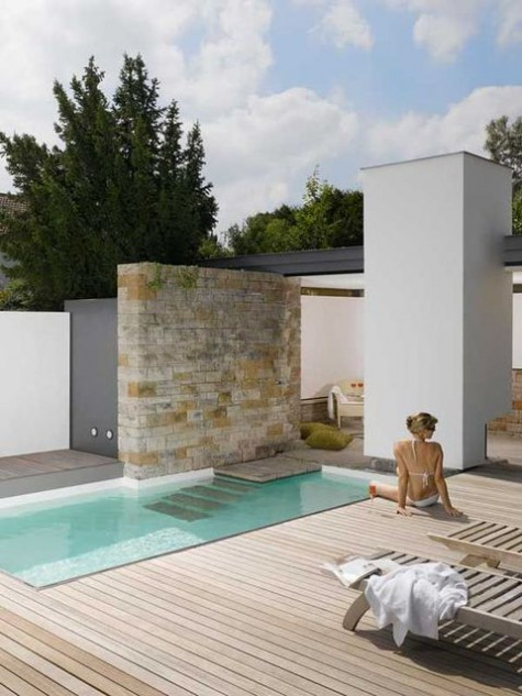 a minimalist outdoor space with a stone wall, a desk, a plunge pool and some simple wooden furniture