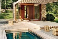 a minimalist wooden backyard with a roof, some furniture items, a built-in plunge pool and a hot tub