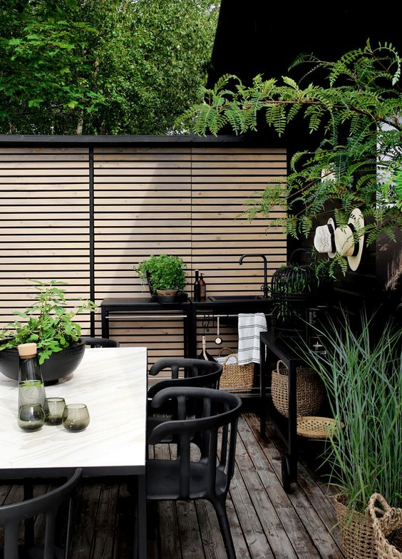 a modern Nordic terrace with a black kitchen space, black furniture, a white table and lots of greenery