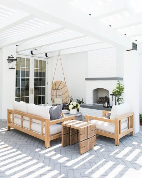 a modern neutral terrace with wooden furniture, a hanging rattan chair, a fireplace and greys feels very welcoming