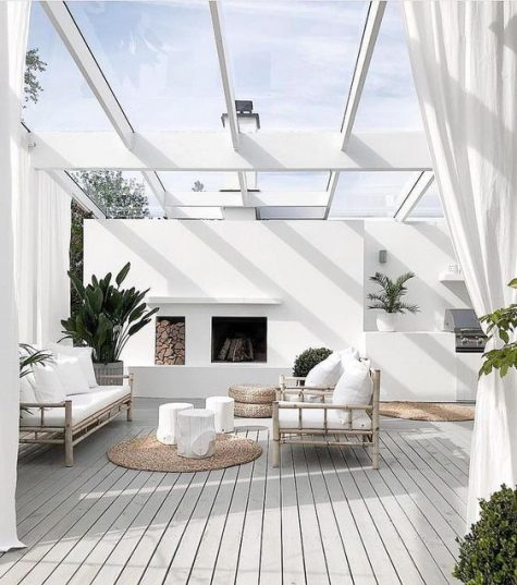 a modern neutral tropical terrace with rattan furniture, a fireplace, jute rugs and white upholstery