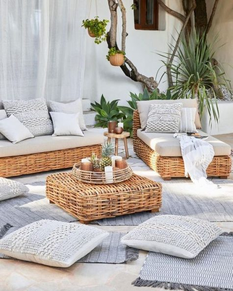 a modern rustic terrace with low wicker furniture, neutral textiles, lots of rugs and throws and greenery