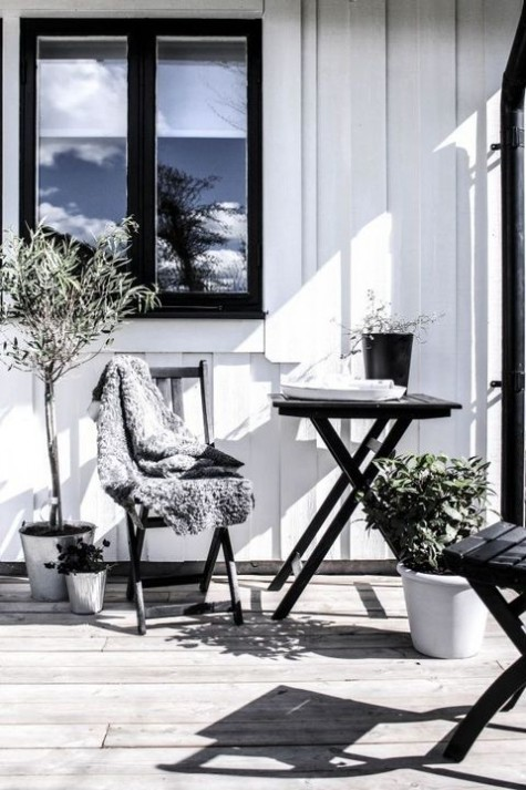 a monochromatic Nordic terrace with black furniture, potted greenery, a folding table looks bold and contrasting
