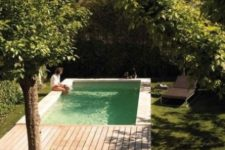a natural and contemporary outdoor space with a deck and a plunge pool plus grass and trees all around