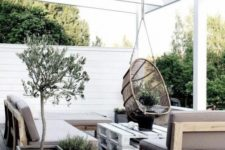 a neutral Scandinavian terrace with simple furniture, a pallet table, a rattan hanging chair and potted greenery