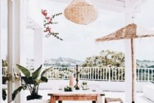 a neutral boho terrace with a wicker lamp, wooden furniture, a jute ottoman and greenery