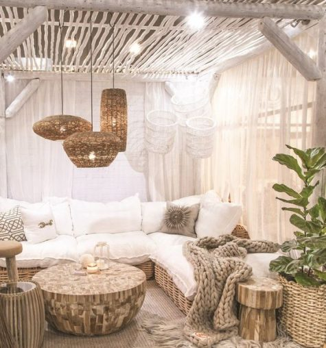a neutral boho terrace with wicker lamps, a large wooden table, a wicker sofa and lots of lights