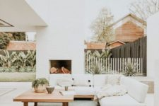 a neutral modern terrace with a fireplace, a pallet sofa and a table plus some greenery