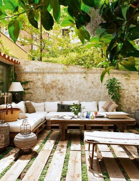 a neutral rustic meets boho terrace with pallet furniture, Moroccan lanterns, lamps and greenery