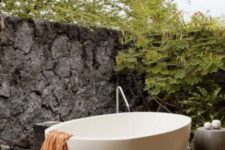 a peaceful outdoor bathroom with a stone wall for privacy, a concrete table and an oval free-standing bathtub