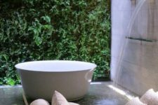 a private courtyard with a living wall, a waterfall shower and a coach by the bathtub