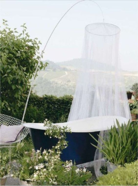 a private space with greenery half walls, a navy tub with a net over it and greenery and blooms all around