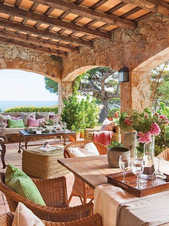 a rustic Mediterranean terrace with wicker furniture, potted greenery and blooms, wooden tables