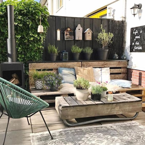 a rustic Scandinavian terrace with reclaimed wood furniture, a green chair, potted plants and birdhouses