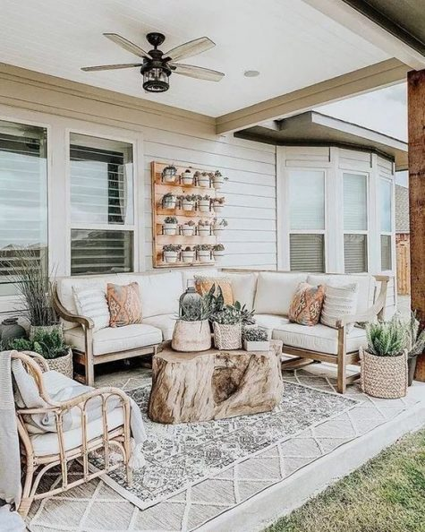 a rustic meets boho neutral terrace with rattan furniture, a tree stump, a vertical garden and layered rugs