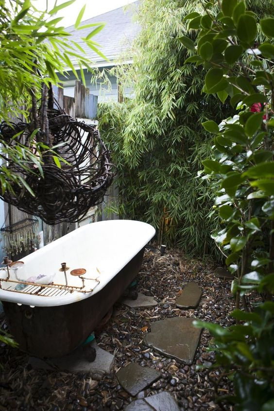 a rustic outdoor bathroom with pebbles and rocks, greenery and walls around plus a vintage tub